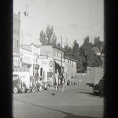 1939: two gentlemen riding their horses through town WYOMING Stock Footage