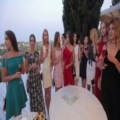 Models in dresses drinking champagne on the terrace at the restaurant Stock Footage