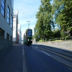 Light daytime traffic on Kanavakatu street, green tram rush towards and pass by Stock Footage