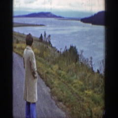 1939: a person wearing long coat standing on the road near to river WYOMING Stock Footage