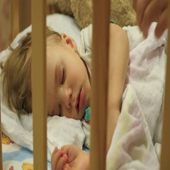 The sweet baby sleeps in a cot. mother covers a blanket Stock Footage