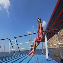 Seductive girl in the red sundress and sunglasses sitting on the ship Stock Footage