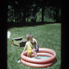1953: siblings playing in an inflatable pool in the garden of their house Stock Footage