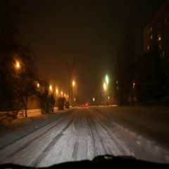 Driving a car along snowbound street at night Stock Footage