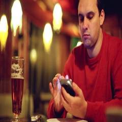 Young man with smartphone drinking beer and reading or sending message at bar or Stock Footage