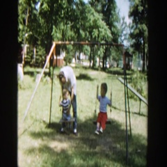 1953: two children swinging on swing set in yard with man WISCONSIN Stock Footage