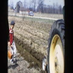 1954: a boy and his father walking behind a tractor in a field WISCONSIN DELLS Stock Footage