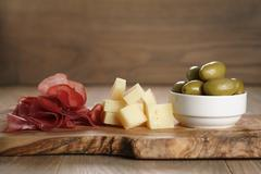 Classic italian antipasti, breasola. olives and parmesan on olive board, shallow Stock Photos