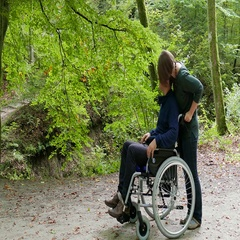 Disabled man in a wheelchair and his wife on a stroll in a park Stock Footage