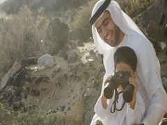 Arab man with his son looking through binoculars. Stock Footage