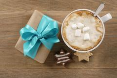 Cup of cappuccino and gift box with azure ribbon on wooden oak table top view Stock Photos