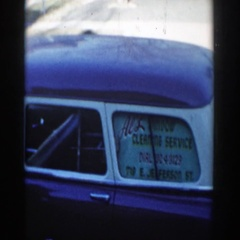 1954: a man stands beside his car, advertising a window cleaning service. Stock Footage