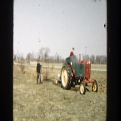 1954: tractor driving through a large grass field while pulling plow WISCONSIN Stock Footage