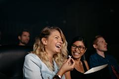 Girls laughing and watching comedy movie Stock Photos