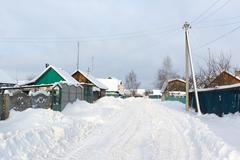 The snowy winter road runs through the village with build Stock Photos