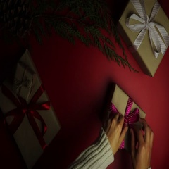 Top view hands wrapping christmas presents on red background from above. Gift Stock Footage
