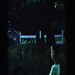 1957: a young boy chasing his dog through the yard while his mom watches Stock Footage