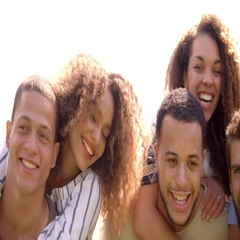 Close up of six young adult friends piggybacking outdoors Stock Footage
