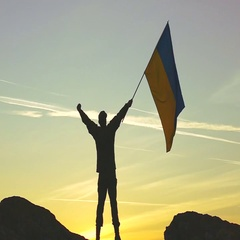 Silhouette of Soldier with Ukrainian Flag Against orange Sky. Slow Motion  Stock Footage