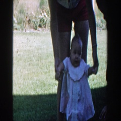 1958: baby trying to walking in the yard, with the help of mom. MICHIGAN Stock Footage