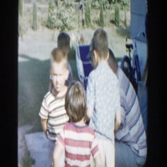 1958: four children standing and playing while being watched by adults MICHIGAN Stock Footage