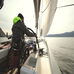 The invalid man in the wheel chair driving a sail boat Stock Footage