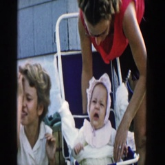 1958: a baby wearing a bonnet at a party sitting in the stroller MICHIGAN Stock Footage
