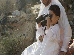 Arab man with his son looking through binoculars. Stock Footage
