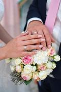 Hand of the bride and groom with rings for wedding bouquet Stock Photos