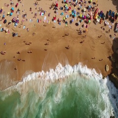 Aerial. Waves filmed from above the beach of Carvoeiro. Tourists on holiday. Stock Footage