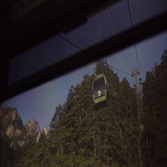 Overhead cable cars passing through green forest Stock Footage