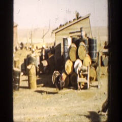 1936: a turkey walking in front of a stack of barrels at a farm CALIFORNIA Arkistovideo