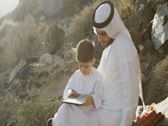 Arab man with son using digital tablet. Arkistovideo