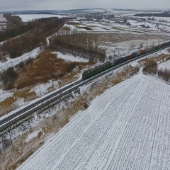 Freight train on the railway in winter. Gasoline, fuel tanks. Aerial shot Stock Footage