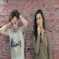 Young man and adult woman stand at brick wall. Man touch hair. Woman touch lips Stock Footage
