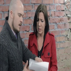 Adult man and woman discuss script on paper. Emotions. Brick wall on background Stock Footage