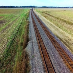 POV aerial view over a train track in rural farm land Stock Footage
