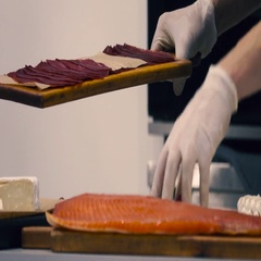 Chef in the restaurant kitchen lays ham and cured meat on a plate Stock Footage