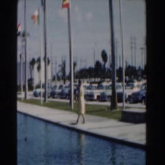 1961: person walking down a walkway near a body of water with the wind blowing Stock Footage