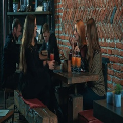 Group of young women at bar 4k video. Female girls friends talking at cafe table Stock Footage
