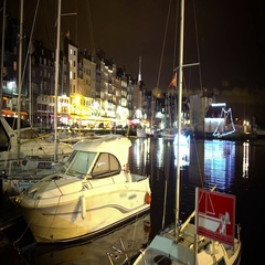 Yachts and boats moored to shore in city harbor at night, illuminated embankment Stock Footage