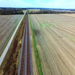 Aerial view following a train track in rural farm land Stock Footage