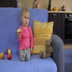 Gorgeous toddler kid child sitting on the sofa and eating big apple fruit Stock Footage