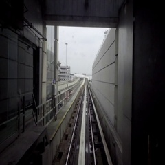 Air train subway exiting tunnel on elevated track Stock Footage