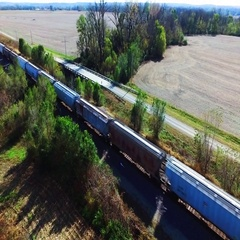 Aerial view overlooking a frieght train passing rural farm land Stock Footage