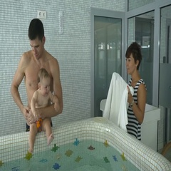 Father and little son complete the water procedures in the child pool Stock Footage