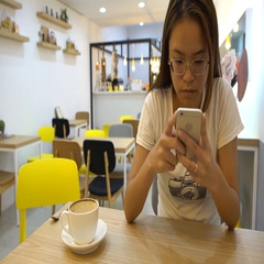 4K Asian Girl Looking At Her Smartphone to chat with people in a coffeeshop-Dan Stock Footage