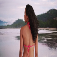 Beautiful mixed race millennial standing on the beach watching waves Stock Footage