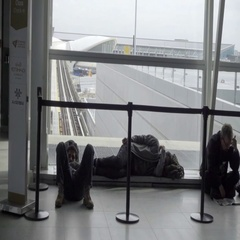 Passengers waiting for layover flight sleeping and sitting on airport floor Stock Footage