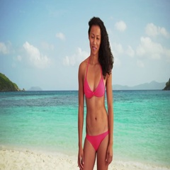 Happy fit Asian millennial wearing a bikini standing on a beach smiling Stock Footage